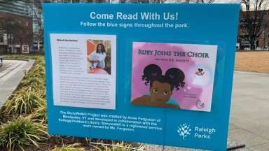 Story walk sign with cover of book and short description in Moore Square