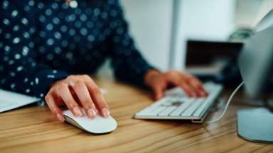 Woman sitting at computer with one hand on mouse and one on the keyboard