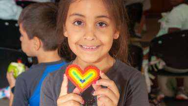 Little girl holding heart craft and smiling