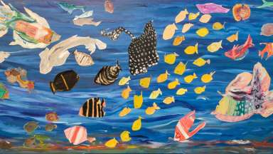 Sea creatures in a variety of papers and colors swimming together in an under the sea view