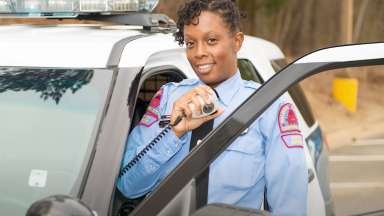 female police officer standing outside their vehicle using a radio