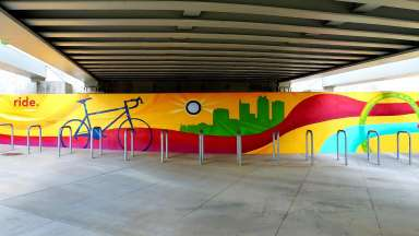 A mural by artist JP Jermaine Powell on wall behind metal bike racks at Raleigh Union Station. The mural features a bicycle, a sun painted around a light fixture, and a silhouette of the city skyline with colorful wavy lines.