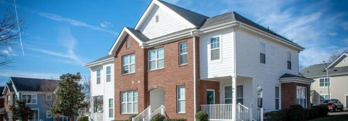 Apartment building with brick and white vinyl siding exterior