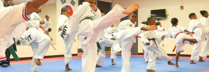 kids kicking high in the air in a martial arts class