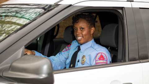 Female Raleigh Police Officer in a patrol car smiling at camera