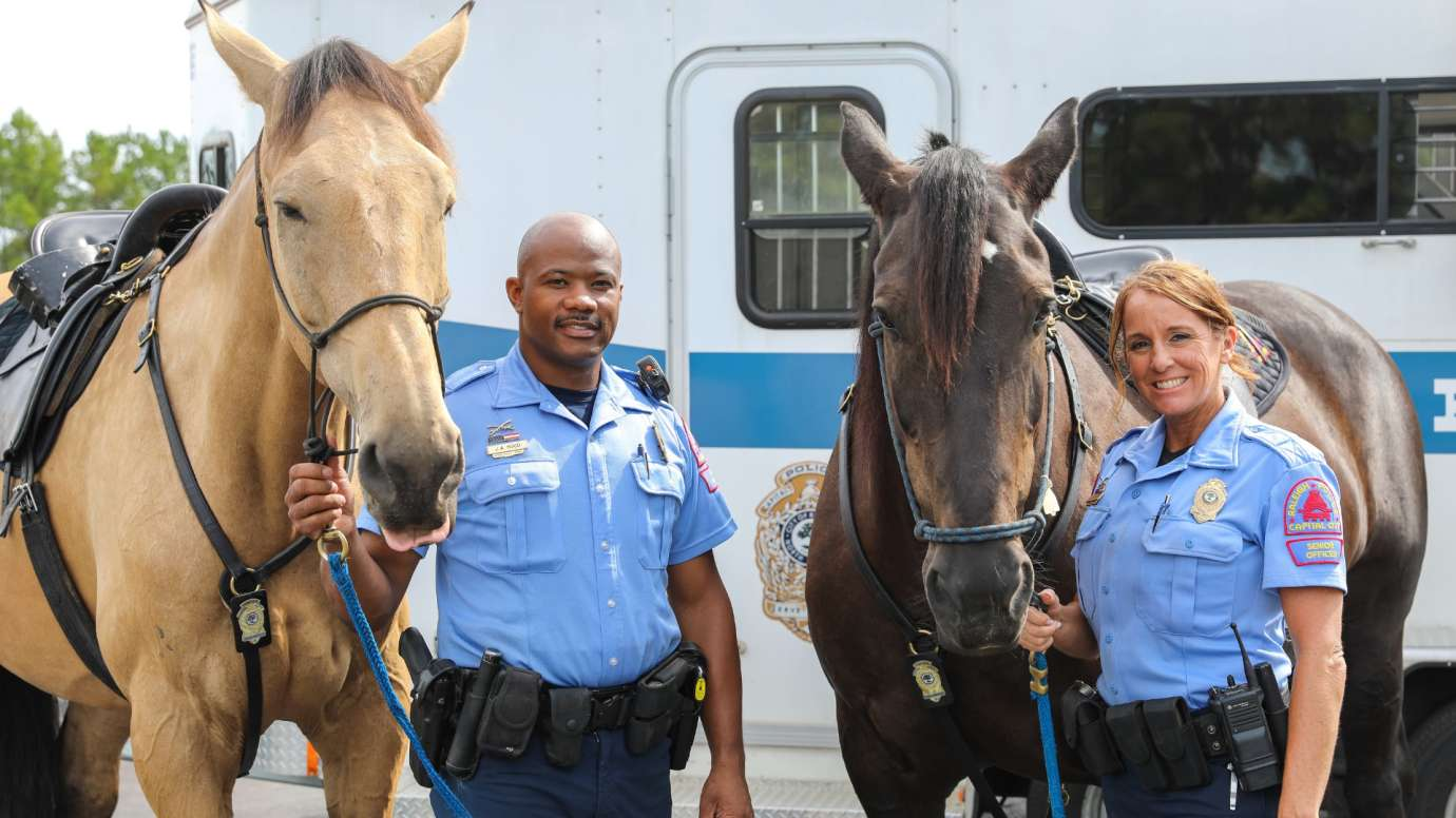 male and female raleigh police mounted officers next to their horses