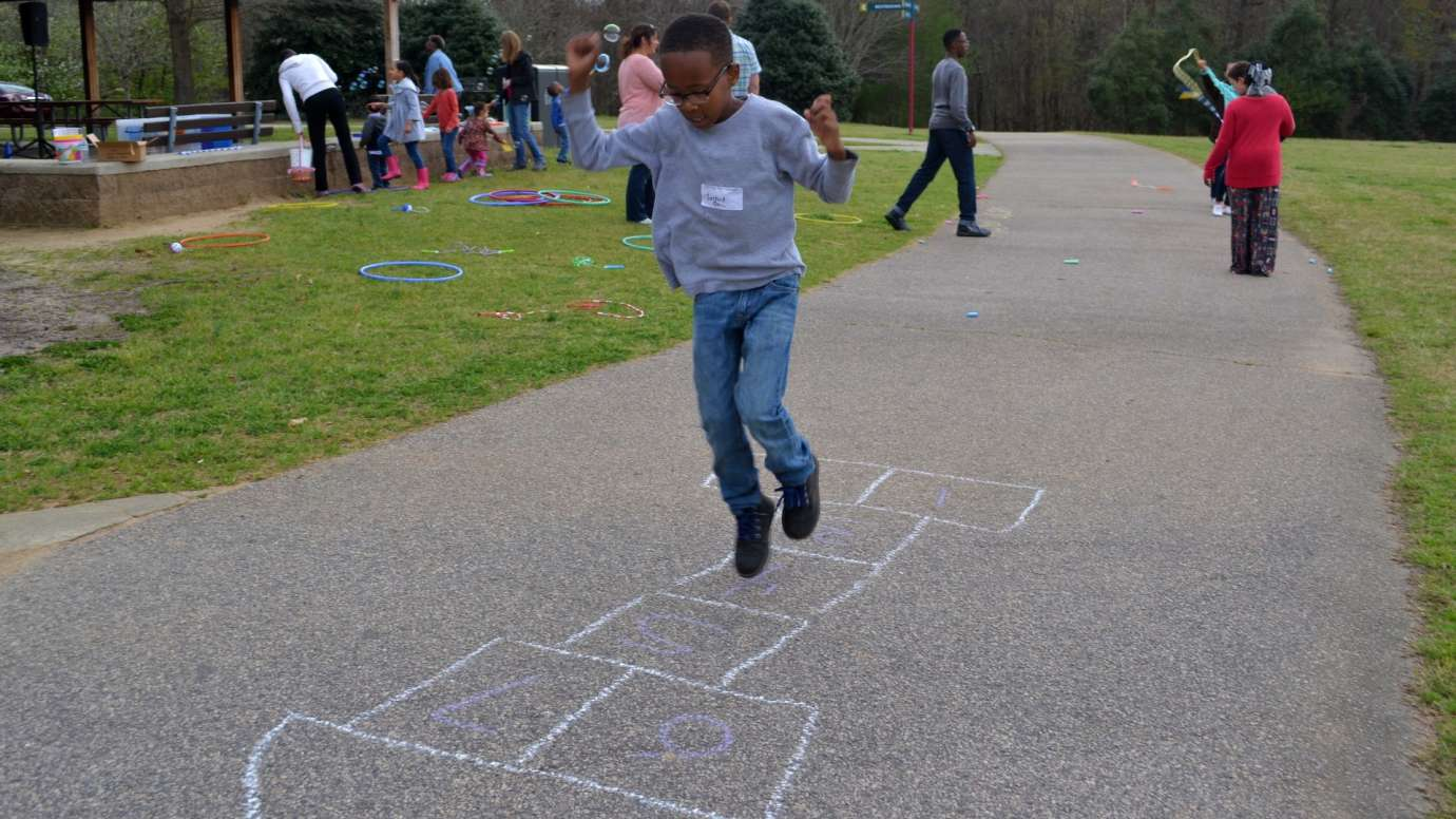 Young boy playing hopscotch on pavement at Anderson Point Park