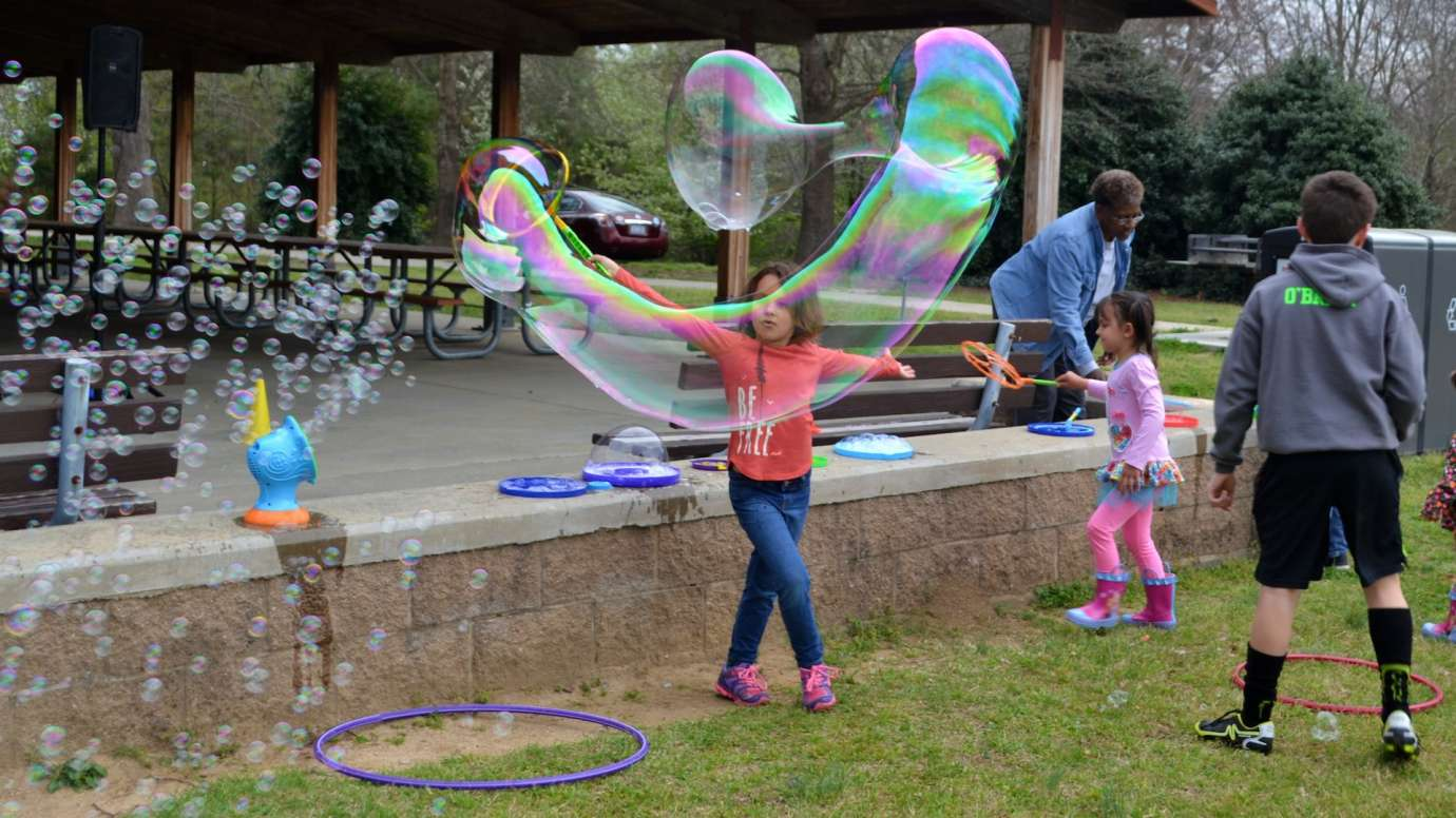 Young girl blows a large oblong bubble in an arc near short stone wall at Anderson Point Park