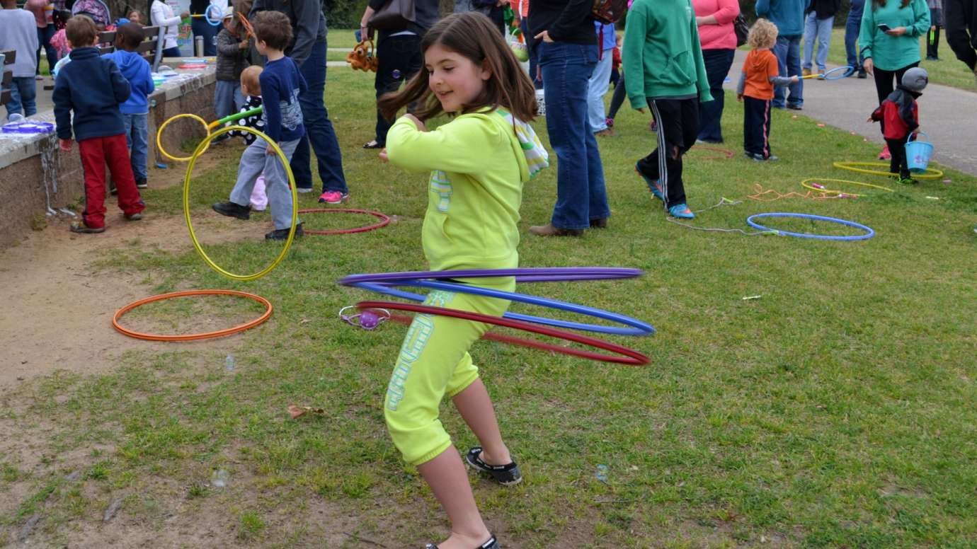 Girl tries using three hula hoop rings at the same time near a picnic shelter at Anderson Point Park