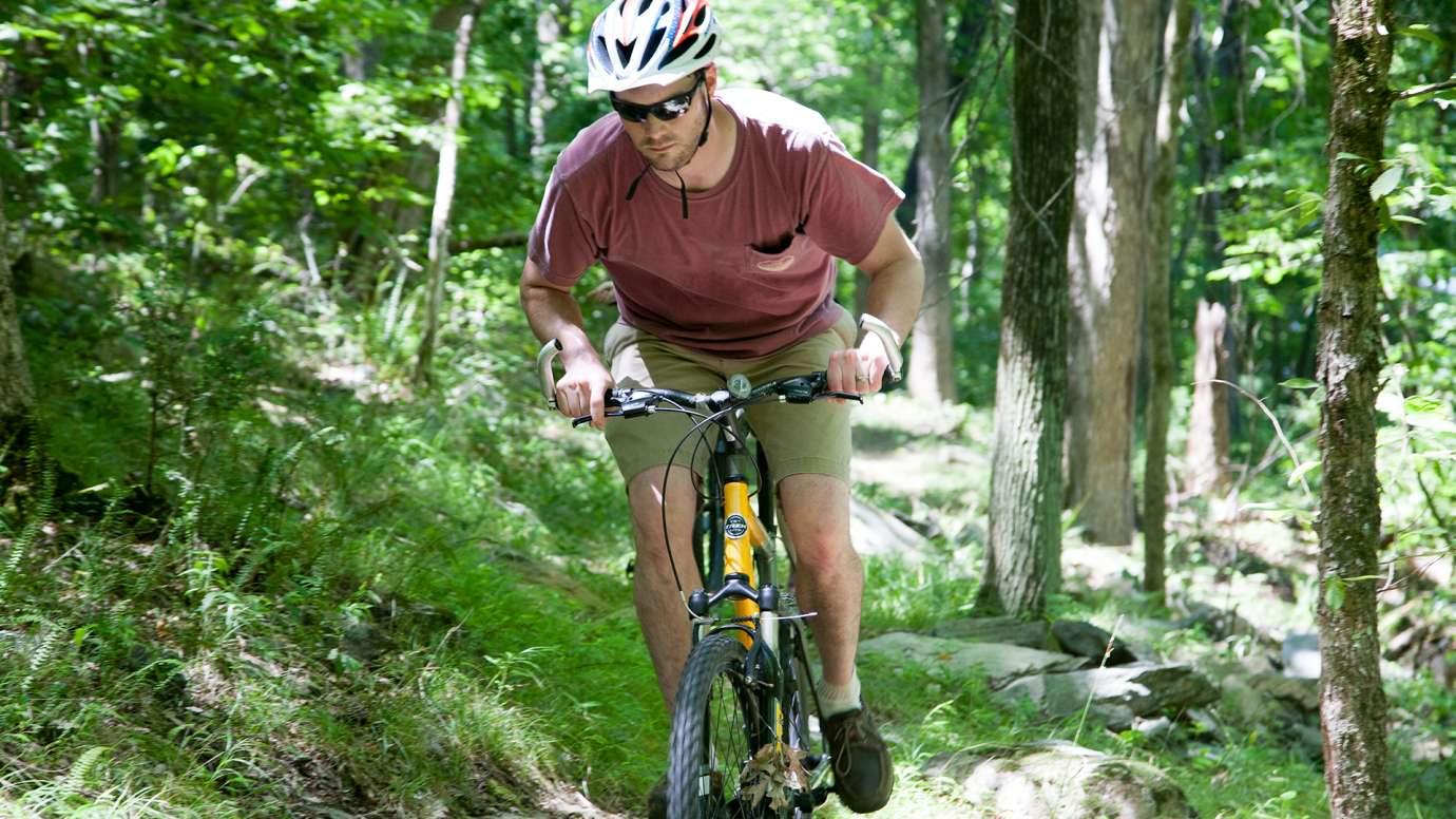 Man mountain biking on trail