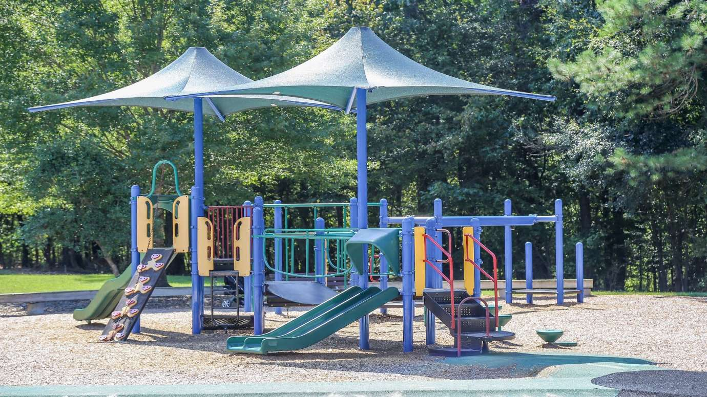 playground structure with slides and other climbing equipment under a canopy
