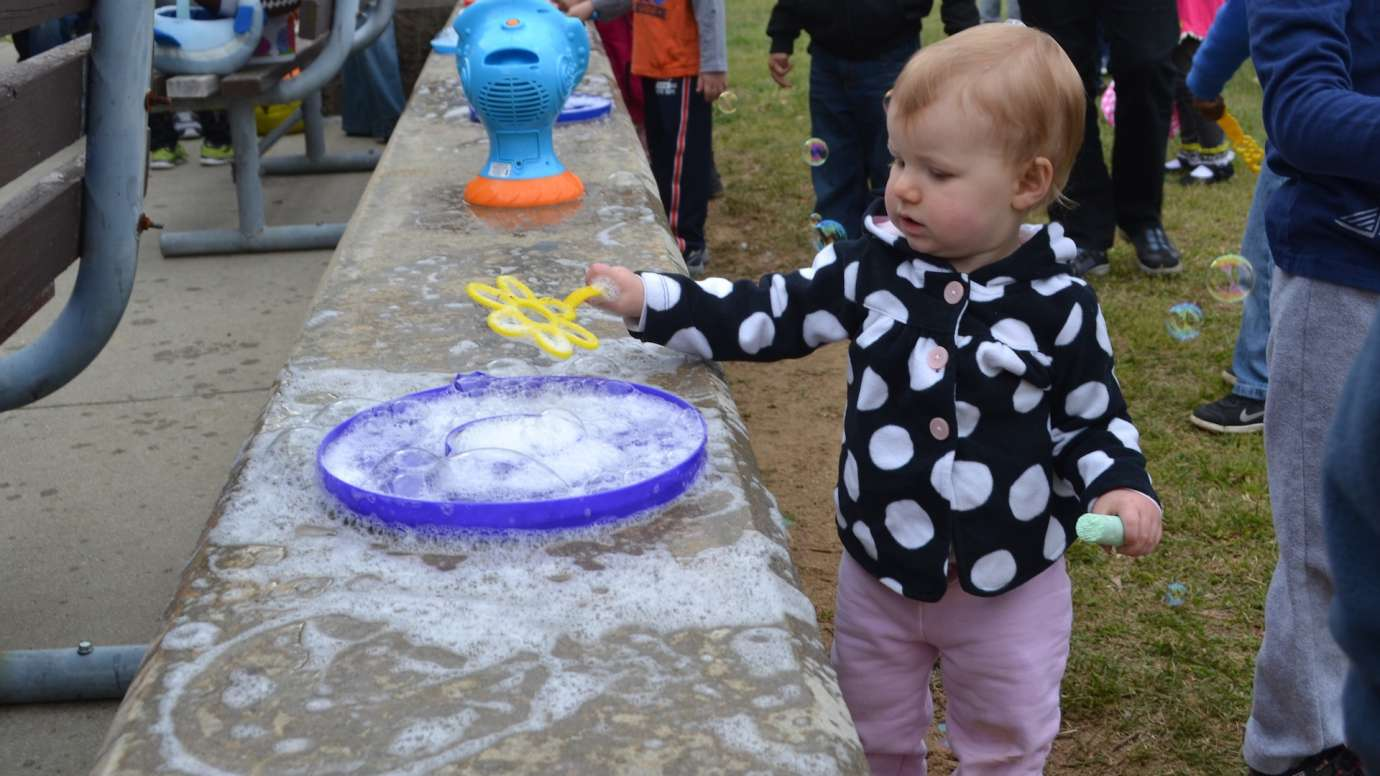 Small toddler girl uses large bubble pan to soak her wand