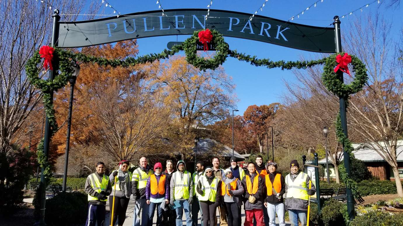 Group of Holiday Express event volunteers under Pullen Park sign.