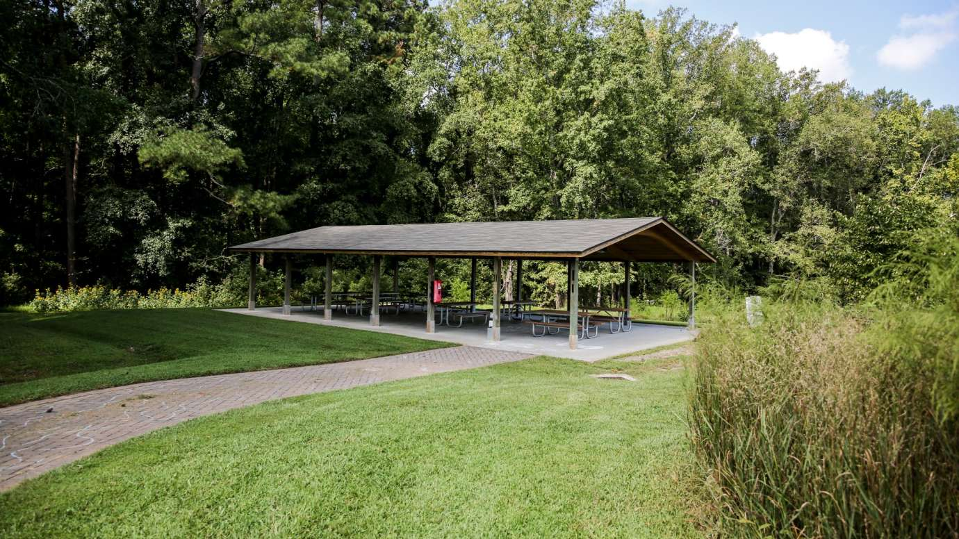 A large outdoor picnic shelter with multiple tables