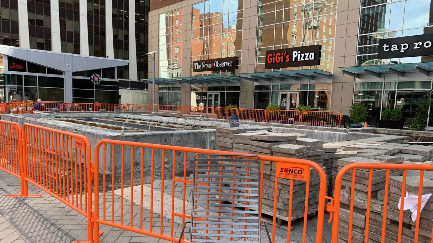 An orange metal construction fence in City Plaza that's surrounding the fountain that will be removed.