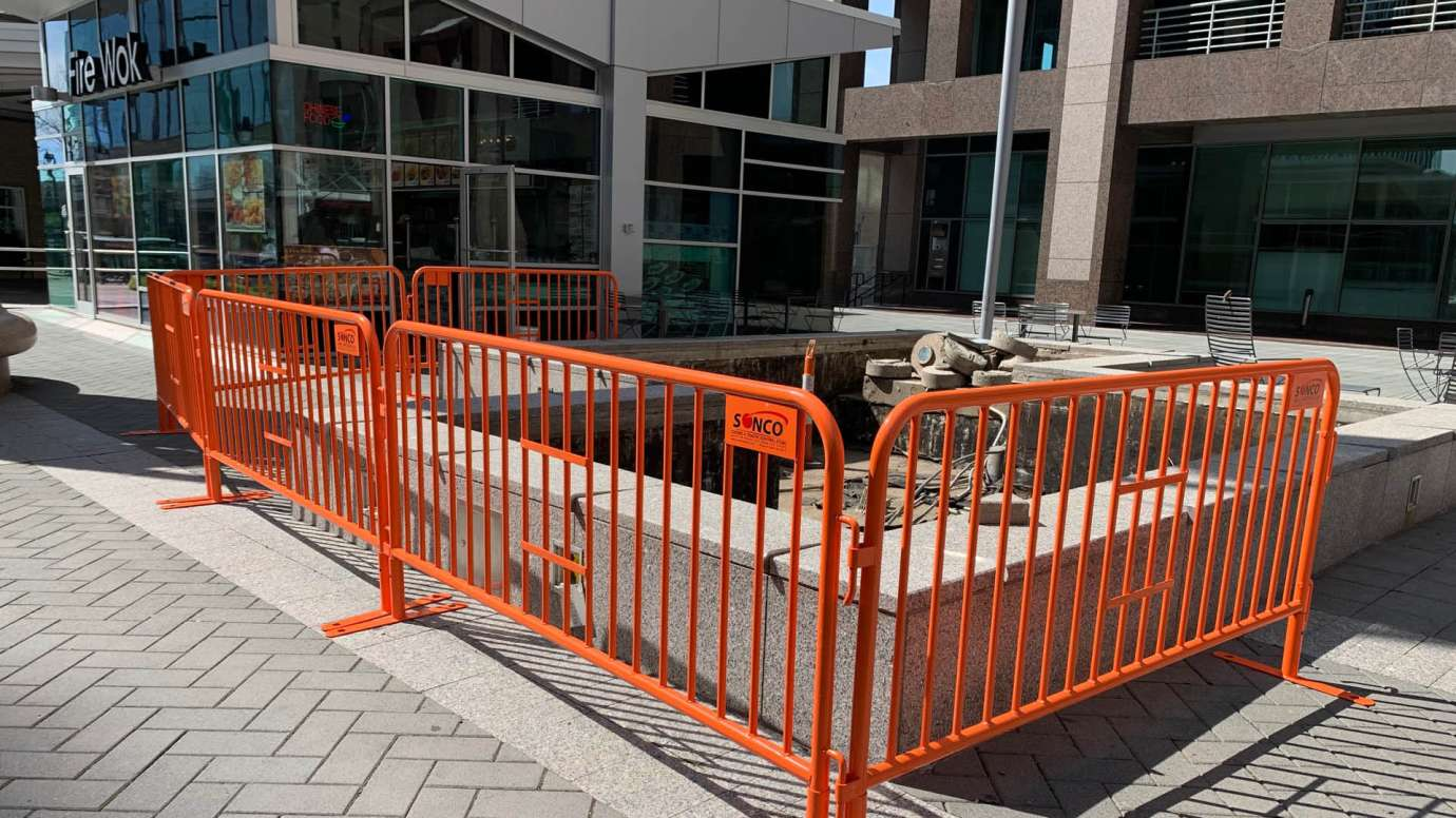 An orange metal construction fence around planters in City Plaza that are being repaired