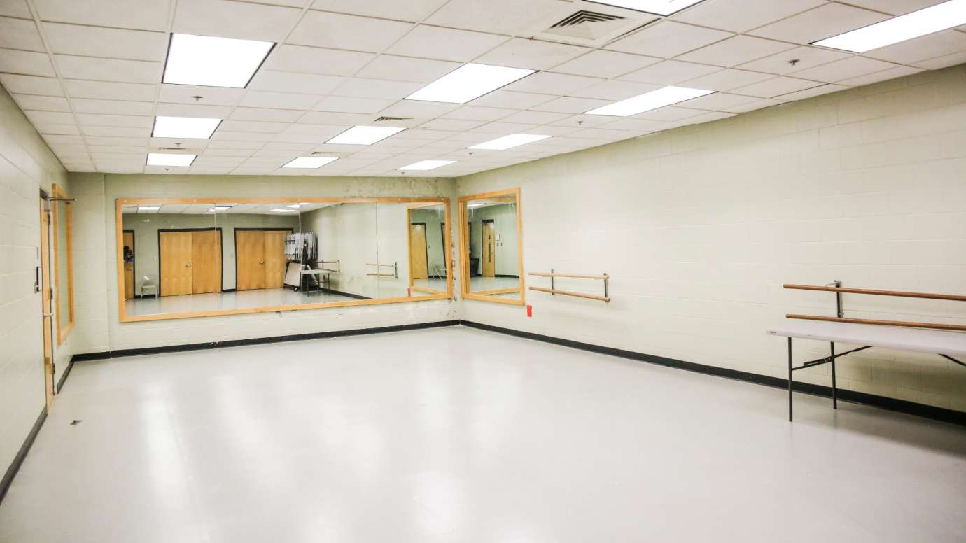 A dance studio with bars and mirrors