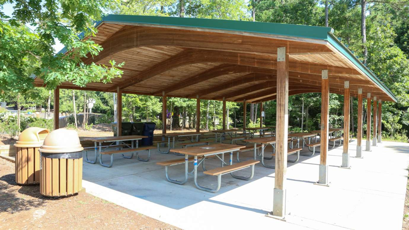 An outdoor picnic shelter with 10 tables