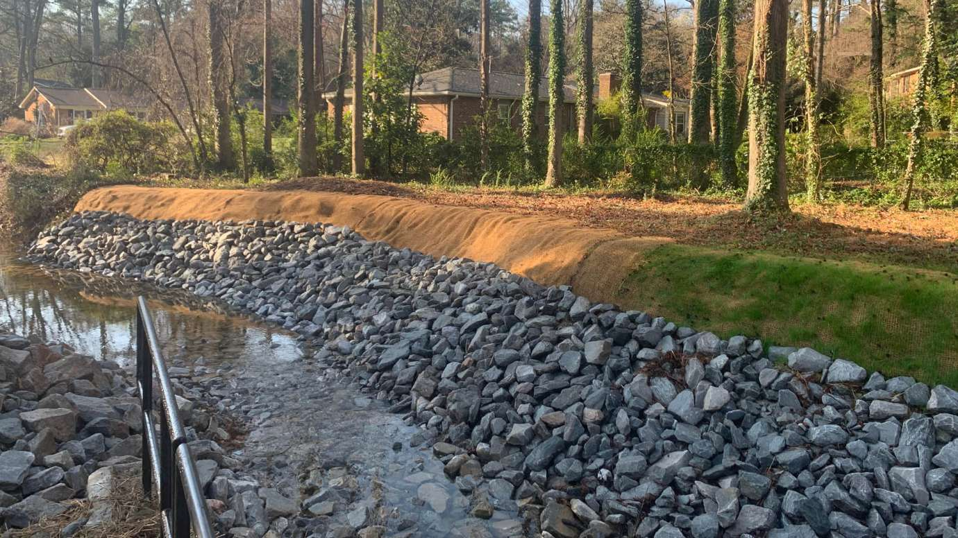 A stream on Swift Drive with repaired streambanks and rock to protect the stream.